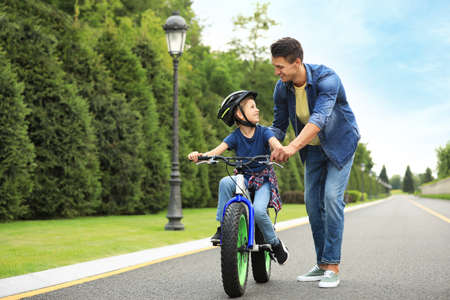 Dad teaching son to ride bicycle outdoors Reklamní fotografie