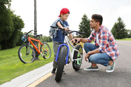 Dad teaching son to ride bicycle outdoors Reklamní fotografie - 132241373