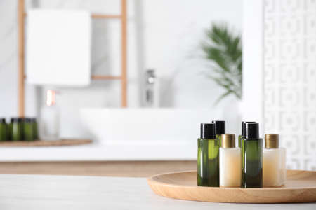 Wooden tray with mini bottles of cosmetic products on white table in bathroom. Space for text