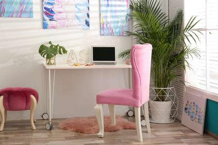 Stylish home workplace with elegant pink chair near window. Interior design 写真素材