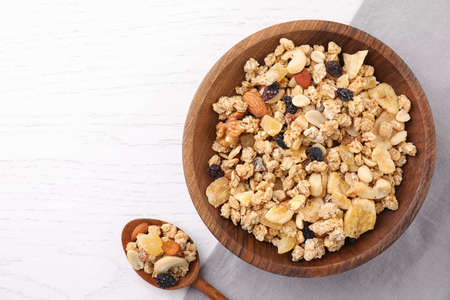 Bowl and spoon with healthy granola on white wooden table, flat lay. Space for text Stok Fotoğraf