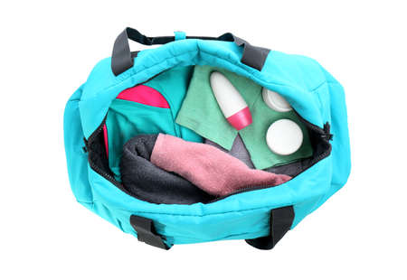 Sport bag with deodorant and clothes on white background, top view