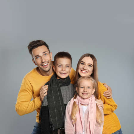 Happy family in warm clothes on grey background. Winter season