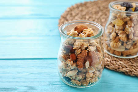 Jars with healthy granola on light blue wooden table. Space for text
