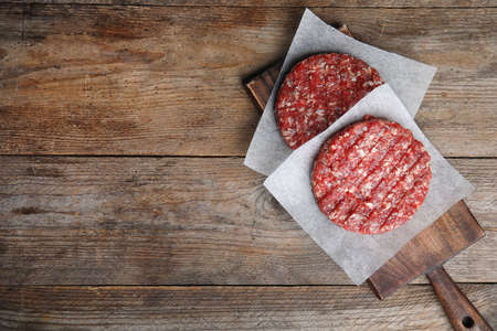 Raw meat cutlets for burger on wooden table, top view. Space for text