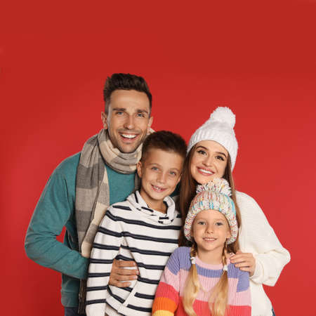 Happy family in warm clothes on red background. Winter season Reklamní fotografie - 132241282