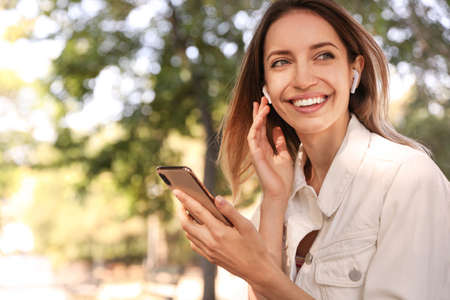Young woman with wireless headphones and mobile device listening to music in park. Space for text