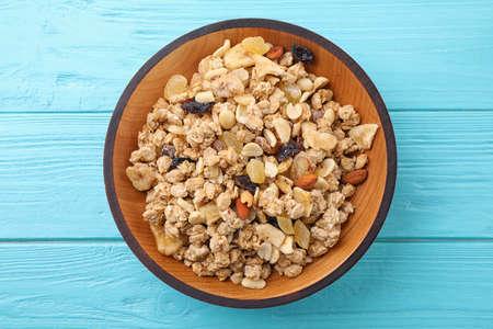 Recipiente con granola saludable en la mesa de madera azul claro, vista superior Foto de archivo