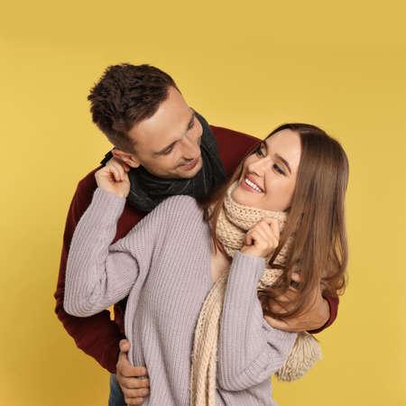Feliz pareja joven en ropa de abrigo sobre fondo amarillo. Temporada de invierno