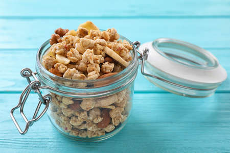 Jar with healthy granola on light blue wooden table
