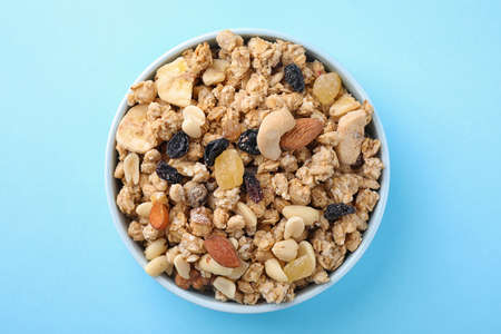 Bowl with healthy granola on light blue background, top view
