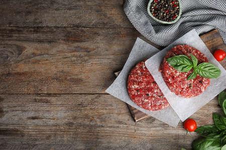 Flat lay composition with raw meat cutlets for burger on wooden table. Space for text