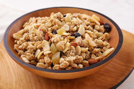 Bowl with healthy granola on wooden plate, closeup