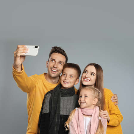 Happy family in warm clothes taking selfie on grey background. Winter season Stock Photo