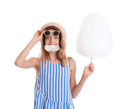 Happy young woman eating cotton candy on white background Reklamní fotografie