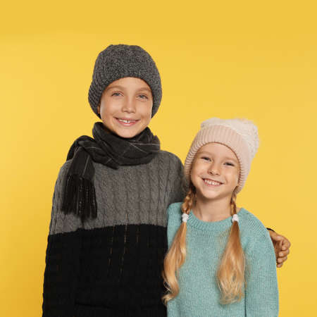 Cute little children in warm clothes on yellow background. Winter season