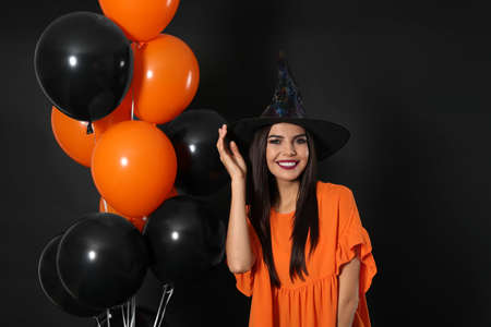 Beautiful woman wearing witch costume with balloons for Halloween party on black background 写真素材