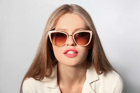 Young woman wearing stylish sunglasses on light background