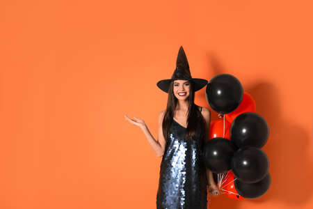 Beautiful woman wearing witch costume with balloons for Halloween party on yellow background, space for text