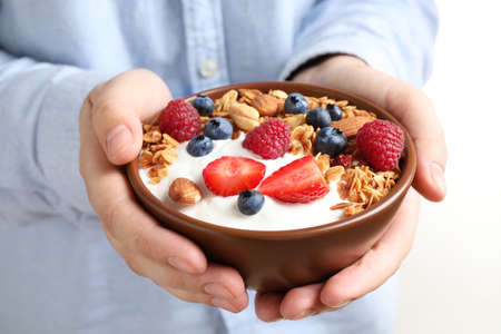 Woman holding tasty homemade granola with yogurt and berries in bowl, closeup. Healthy breakfast