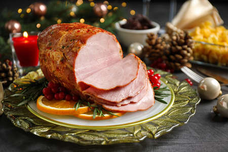 Plate with delicious ham served on grey table. Christmas dinner
