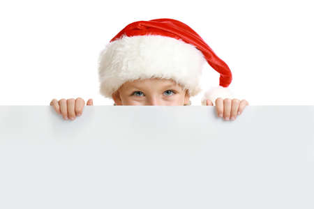 Happy child in Santa hat peeping out of blank banner on white background. Christmas celebration