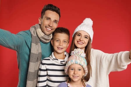 Happy family in warm clothes on red background. Winter season Reklamní fotografie