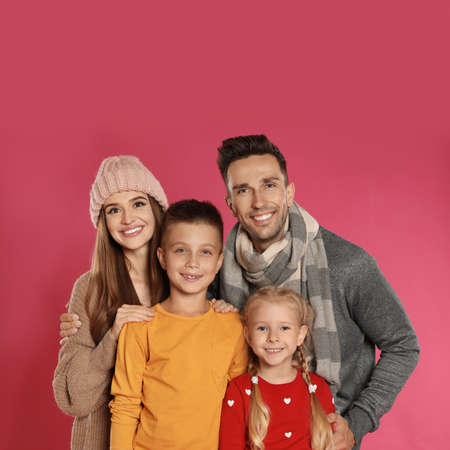 Happy family in warm clothes on pink background. Winter season