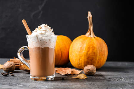 Pumpkin spice latte with whipped cream and cinnamon stick in glass cup on grey table