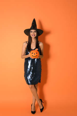 Beautiful woman wearing witch costume with Jack OLantern candy container for Halloween party on yellow background