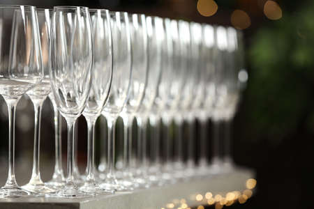 Set of empty glasses on grey table against blurred background