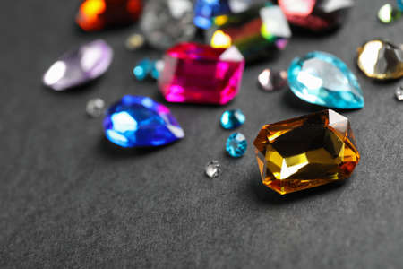 Different beautiful gemstones on black background. Space for text