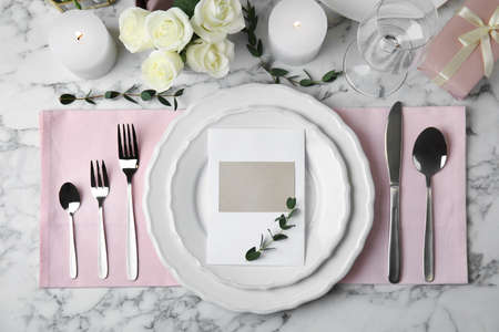 Elegant festive table setting with blank card on white marble background, flat lay
