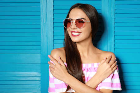 Beautiful woman in red sunglasses near blue wooden folding screen