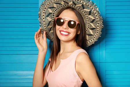 Beautiful woman wearing sunglasses and hat near blue wooden folding screen