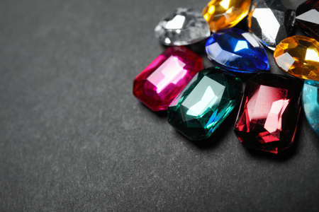 Pile of different beautiful gemstones on black background, closeup. Space for text