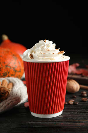 Paper cup with tasty pumpkin spice latte on black wooden table