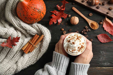 Woman holding cup with tasty pumpkin spice latte at black wooden table, top view