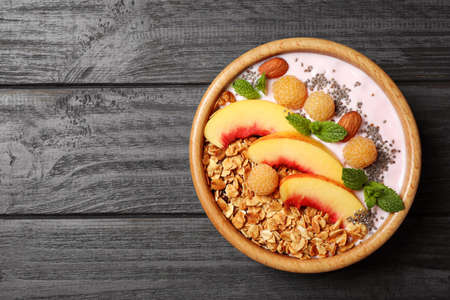 Healthy homemade granola with yogurt on grey wooden table, top view. Space for text