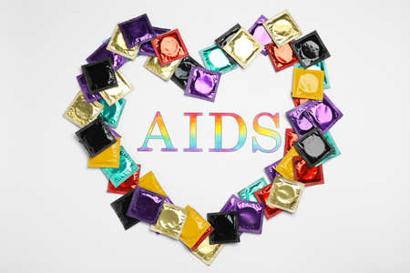 Frame made of colorful condoms with word AIDS inside on white background, top view. Safe sex