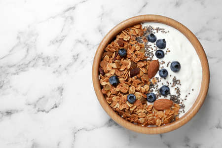 Tasty homemade granola served on white marble table, top view with space for text. Healthy breakfast