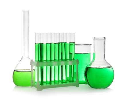 Laboratory glassware with green liquid on white background