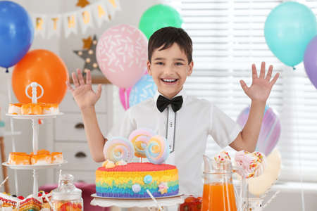 Happy boy at table with treats in room decorated for birthday party Reklamní fotografie