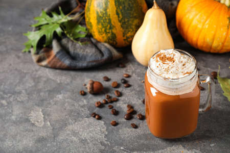 Mason jar with tasty pumpkin spice latte on grey table. Space for text
