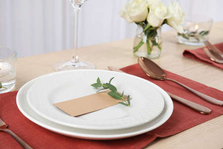 Elegant festive table setting with blank card in restaurant