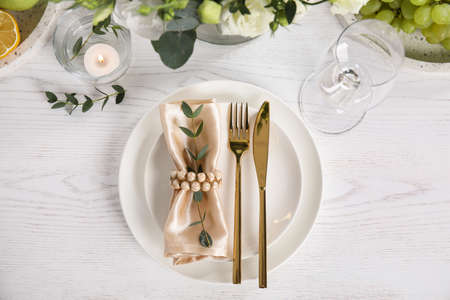 Elegant festive table setting on white wooden background, flat lay