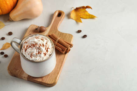 Cup with tasty pumpkin spice latte on light table, space for text