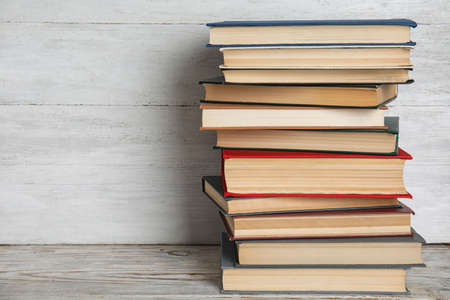 Stack of hardcover books on wooden table against white background. Space for text