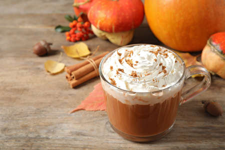 Glass cup with tasty pumpkin spice latte on wooden table, space for text Stock fotó