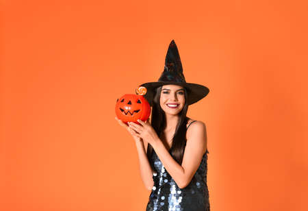 Beautiful woman wearing witch costume with Jack OLantern candy container for Halloween party on yellow background, space for text
